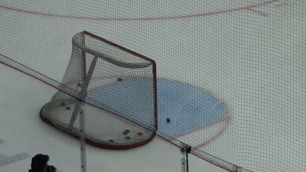 Hokejista zastřelí několik puků do cíle v bráně, detail