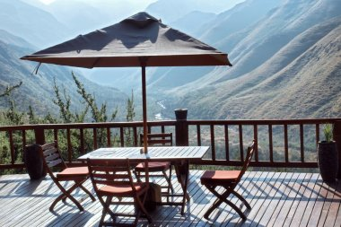Table and chairs under umbrella on terrace against blue mountain