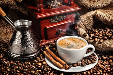 cup of coffee, grinder, turk and coffee beans on brown backgroun