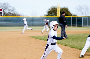 Youth baseball player running bases.