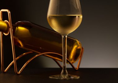 Glass of white wine and white wine bottle  on a metal wine rack