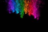 Padající barevné prášek izolovaných na černém pozadí
