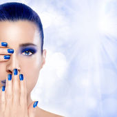 Photo Beautiful Girl in Blue with Hands on Her Face. Nail Art and Make