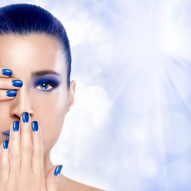 Beautiful Girl in Blue with Hands on Her Face. Nail Art and Make