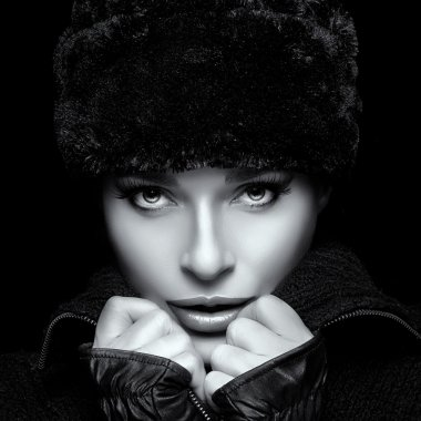 Winter Fashion Portrait. Closeup of Young Woman in Fur Hat