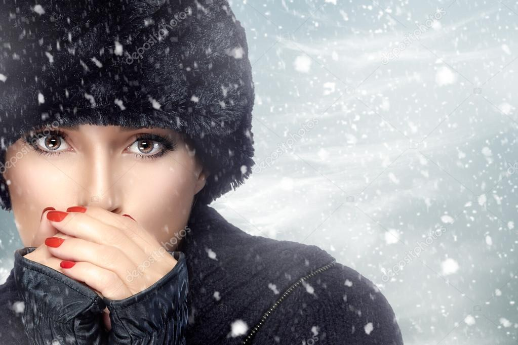 Winter Beauty Fashion. Girl in Warm Clothes on a Snowstorm