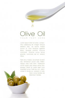 Virgin olive oil dripping from a spoon and olive seeds