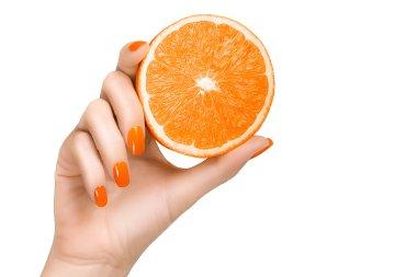 Hand with Orange Nails Holding an Orange Fruit