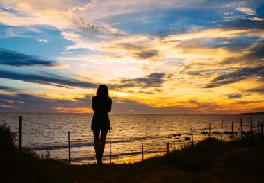 Silhouette of Woman Stands at the Beach on Sunset