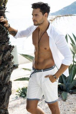 Handsome male model wearing white shirt posing