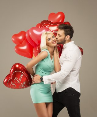 Kissing couple with red balloons