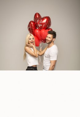Attractive couple with red balloons
