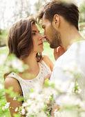 Líbající se pár v rozkvetlé zahradě