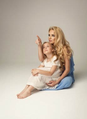 Mother showing empty space to daughter