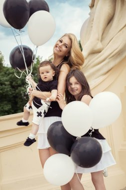 mother with children having a fun with baloons