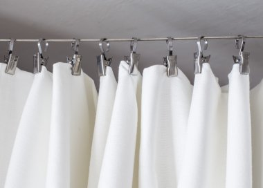 Cream-colored curtain hanging on a string on metal hooks illuminated by daylight