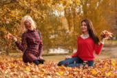 Fotografie blondýna a bruneta ženy v podzimní listí