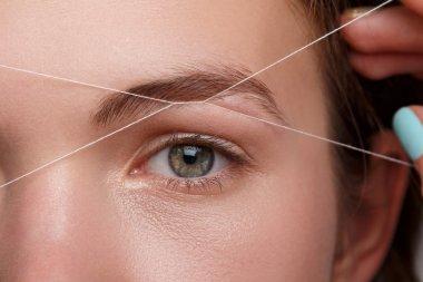 Eyebrow correction with a white thread
