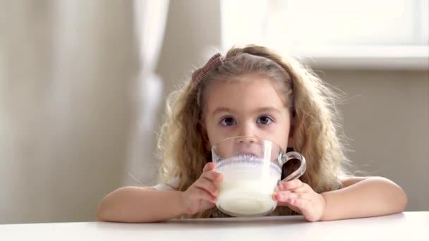 Roztomilé blondýny holčička sedí v kuchyni, drží sklo pití mléka nebo jogurt těšit ráno báječný nápoj s úsměvem na kameru, koncept růstu dítěte, zdravý životní styl, zdravotní péče
