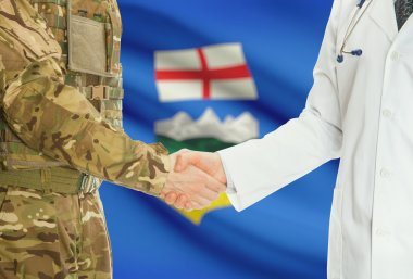 Military man in uniform and doctor shaking hands with Canadian provincies and territories flags on background - Alberta
