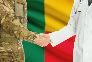Military man in uniform and doctor shaking hands with national flag on background - Benin