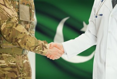 Military man in uniform and doctor shaking hands with national flag on background - Pakistan