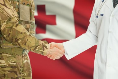 Military man in uniform and doctor shaking hands with national flag on background - Tonga