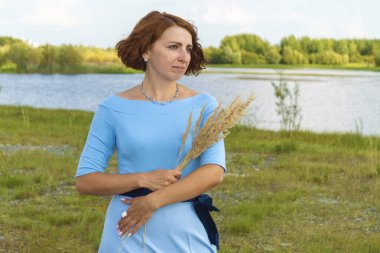 Woman in blue dress with bouquet of flowers. Stands on road against green bank of river.