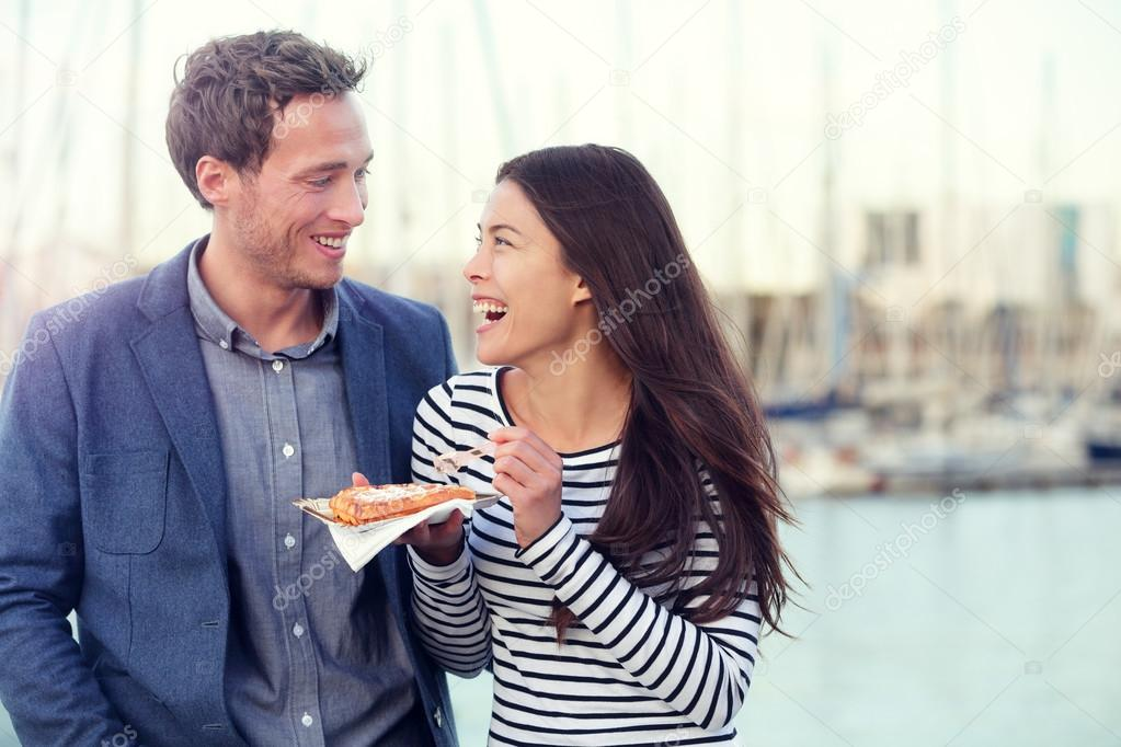 Couple eating waffles on date enjoying food snack. Romantic man and woman  laughing having fun outdoors. Multiracial couple, Young Caucasian man and  Asian ...