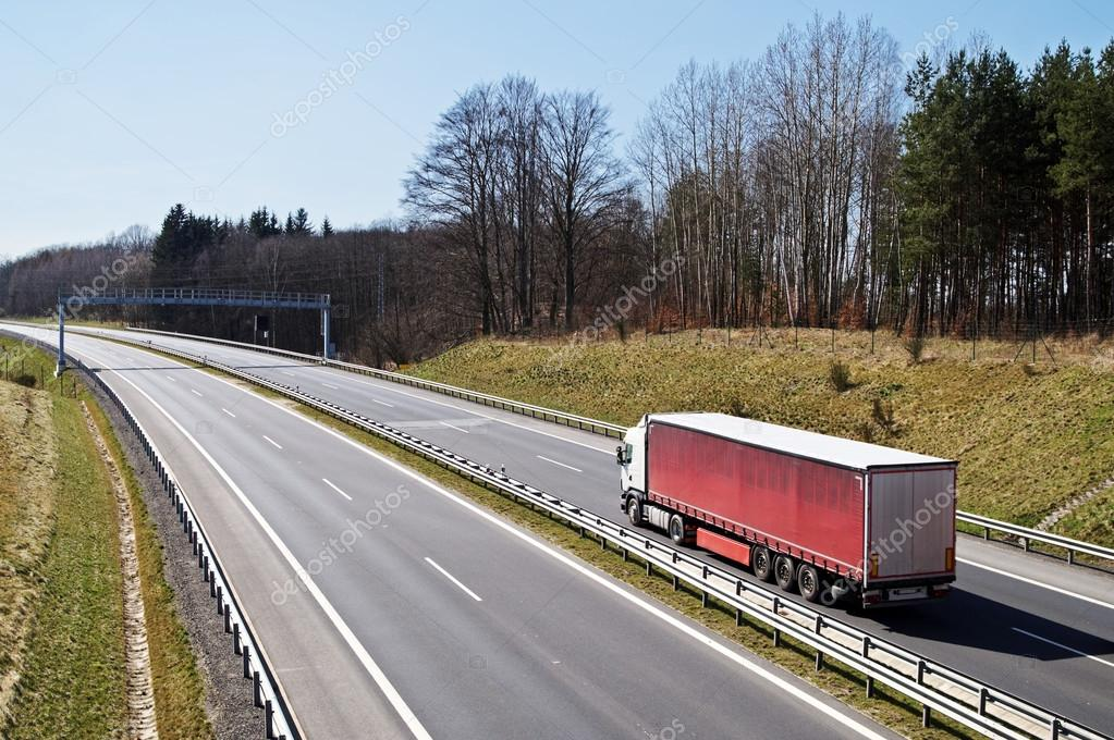 A lone truck arriving to the electronic toll gate on an asphalt highway in the countryside in early spring