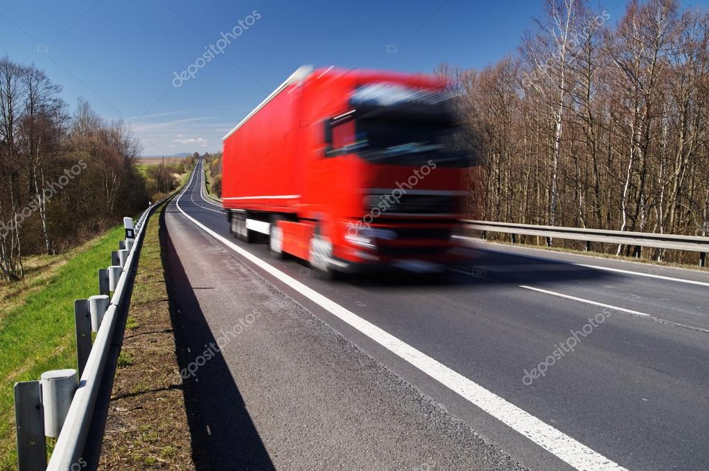Speeding motion blur red truck on asphalt road in a rural landscape