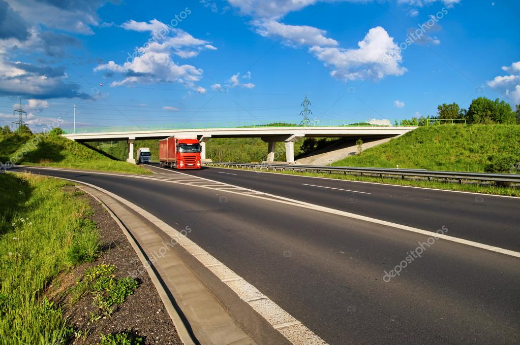 Bridge over an empty highway in the countryside, under a bridge passing two trucks