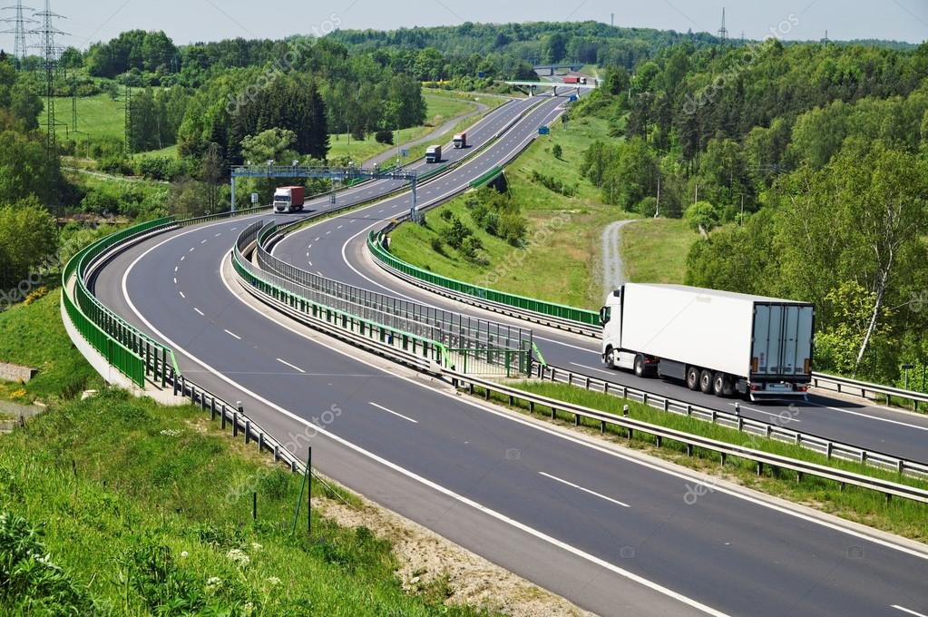 The highway between woods, moving trucks, electronic toll gates