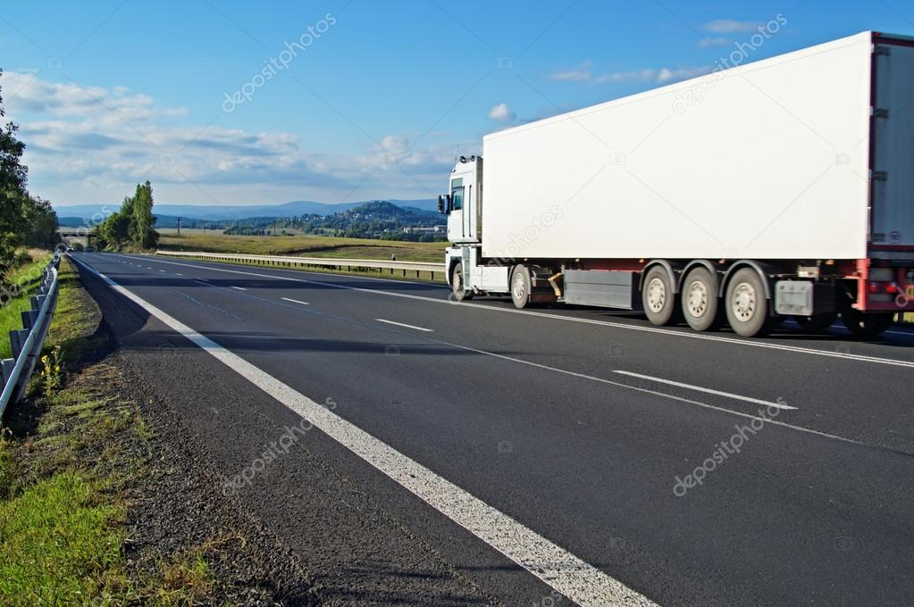 White truck driving on the road a rural landscape