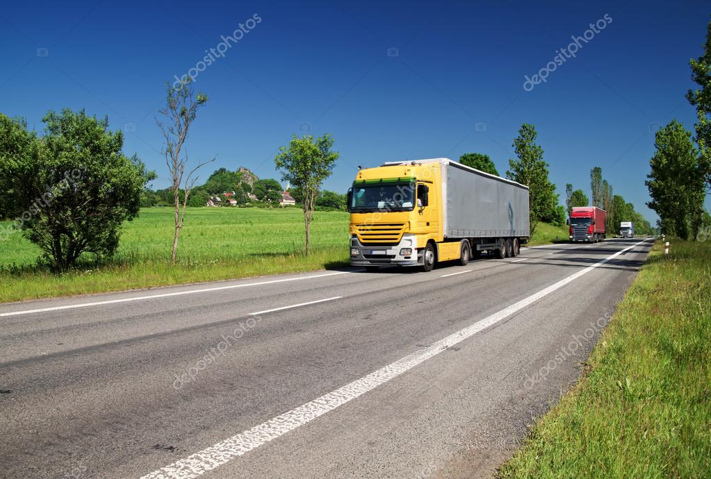 Road lined with trees in a rural landscape, three passing colored trucks