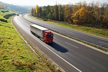 The highway between deciduous forests with leaves in fall colors, the highway ride three trucks