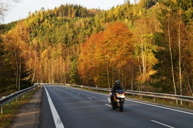 Asphalt road in the autumn landscape with a ride motorcycle, over the road forested mountain