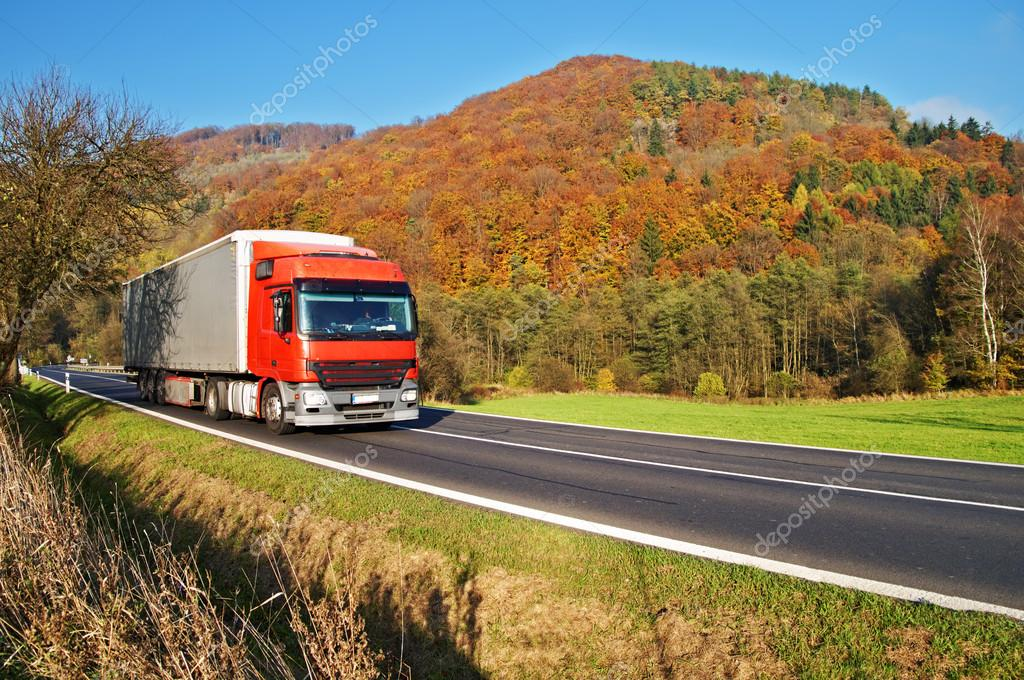 Red truck on the road under the wooded mountain of colorful autumn colors