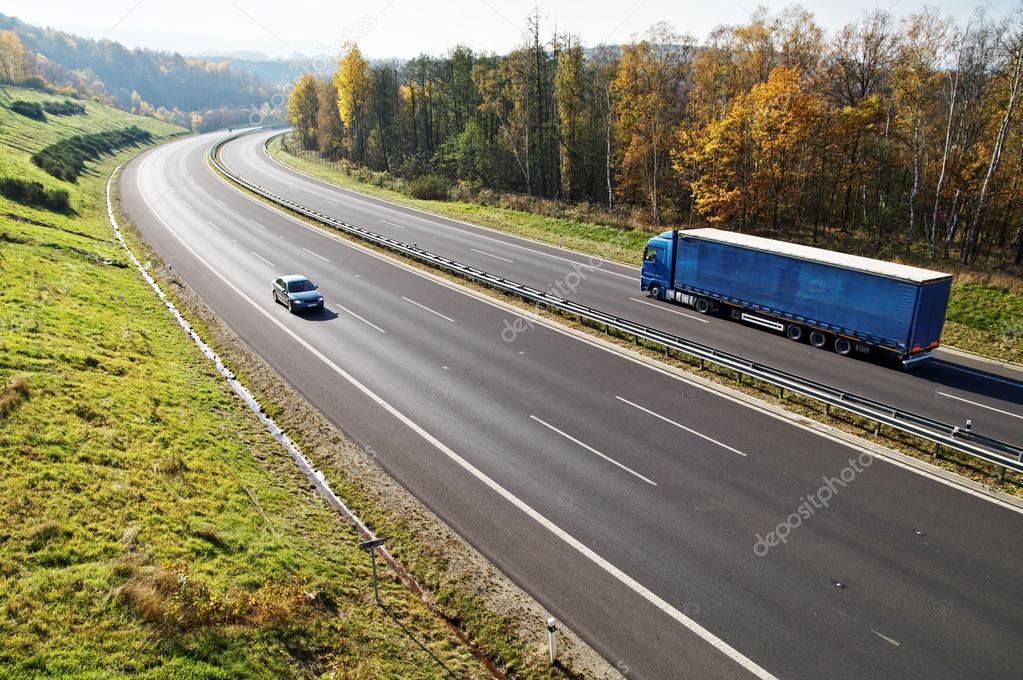 The highway between deciduous forests with leaves in fall colors, the highway goes blue truck and a passenger car