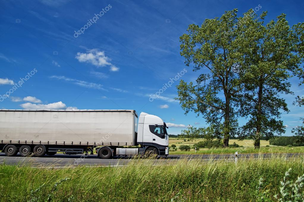 Rural landscape with white truck on the road