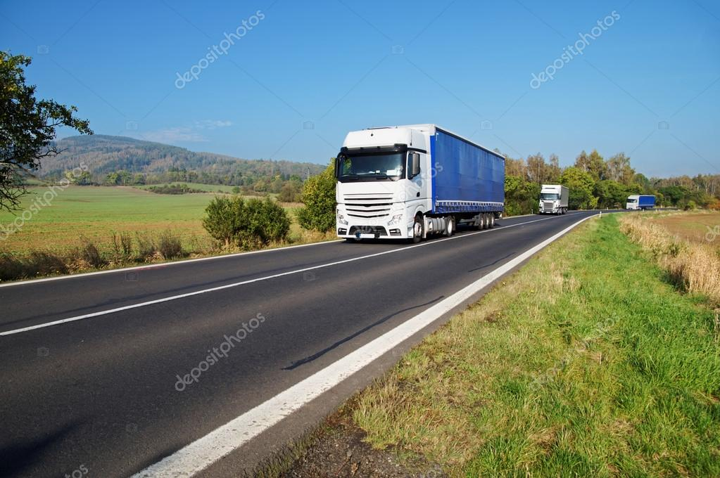Three white trucks on the road in the countryside