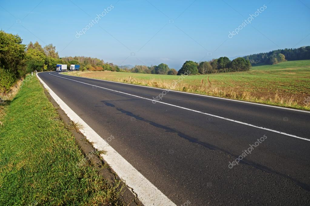 Asphalt road in the countryside, blue and white truck coming around in the distance the bend