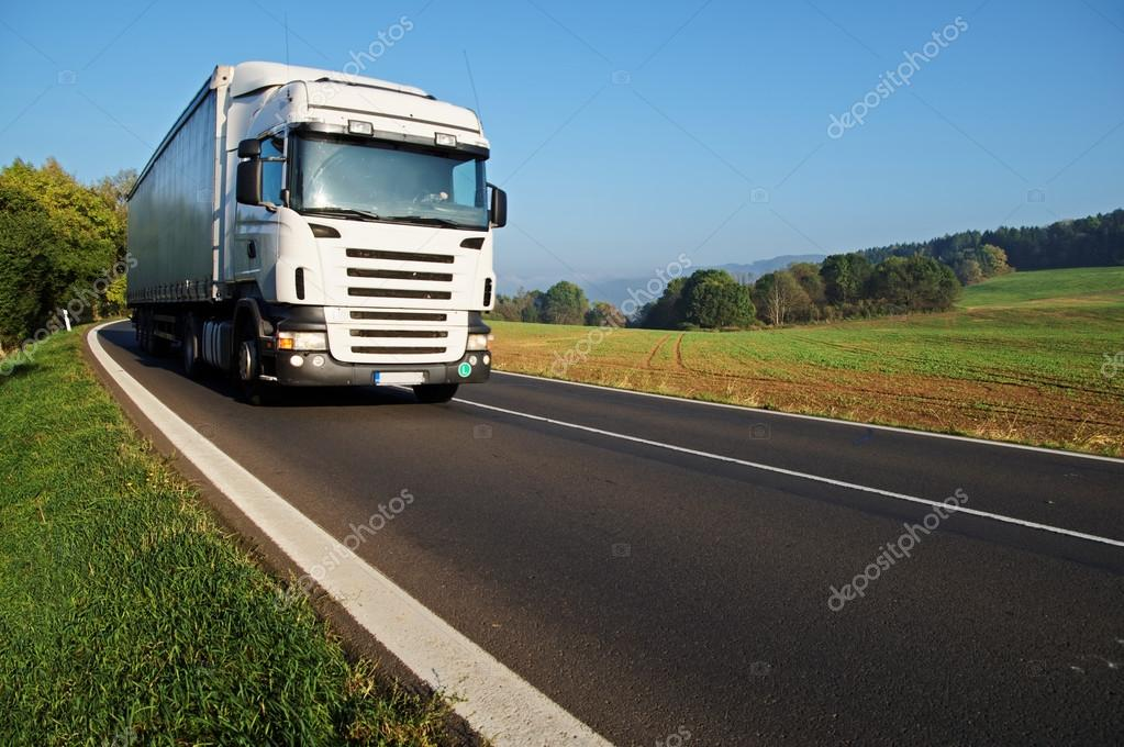 White truck on the road in the countryside