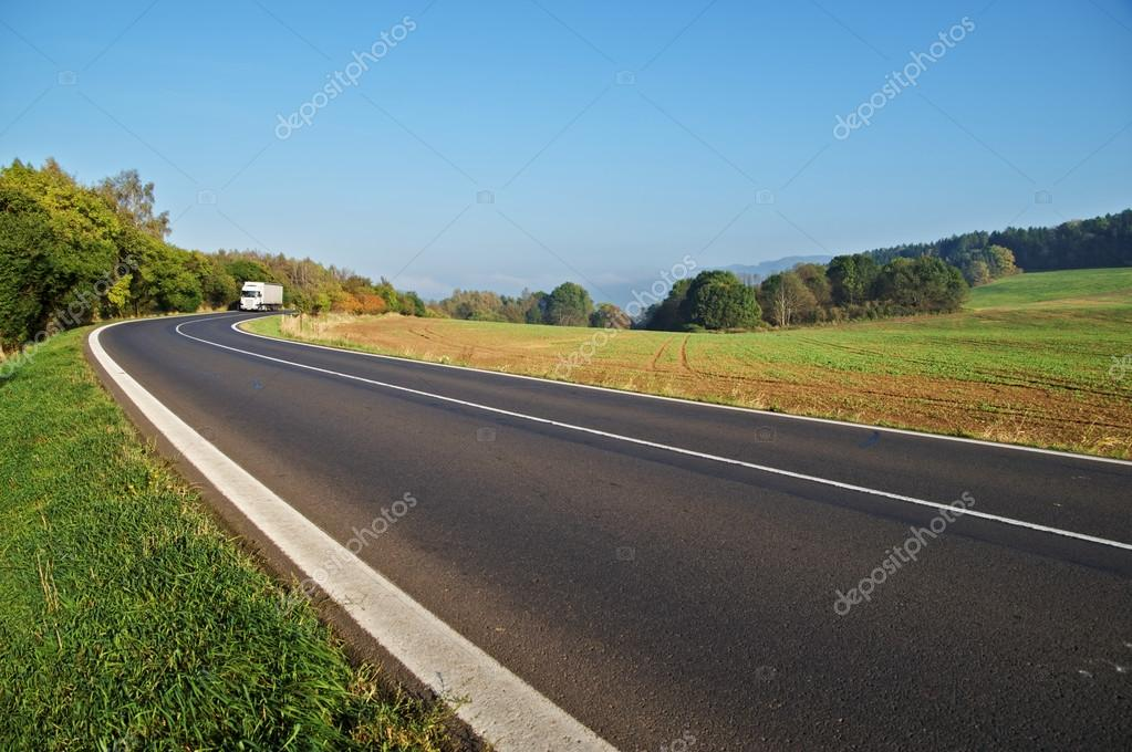 Asphalt road in the countryside, white truck coming around in the distance the bend