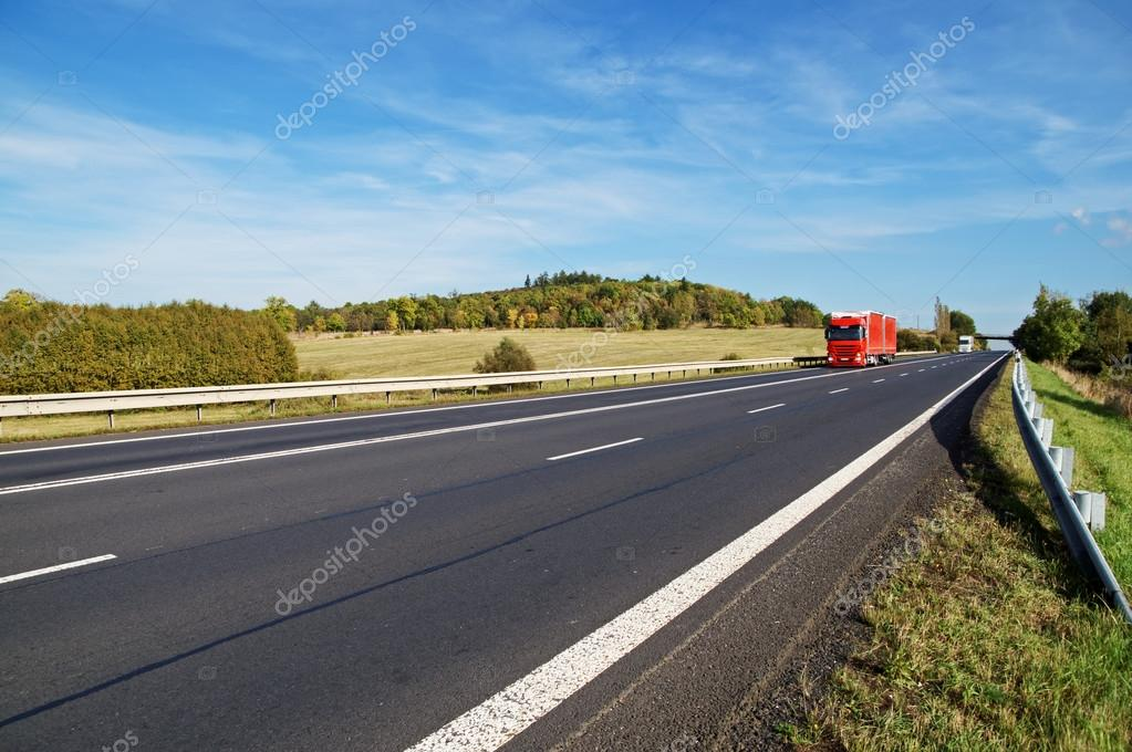 Asphalt road with oncoming trucks in countryside, early autumn colors