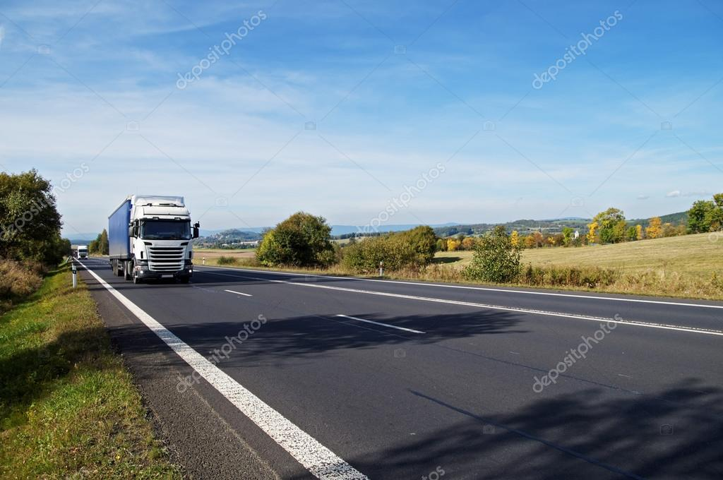 Asphalt road in a rural landscape. The arriving two white trucks on the road.