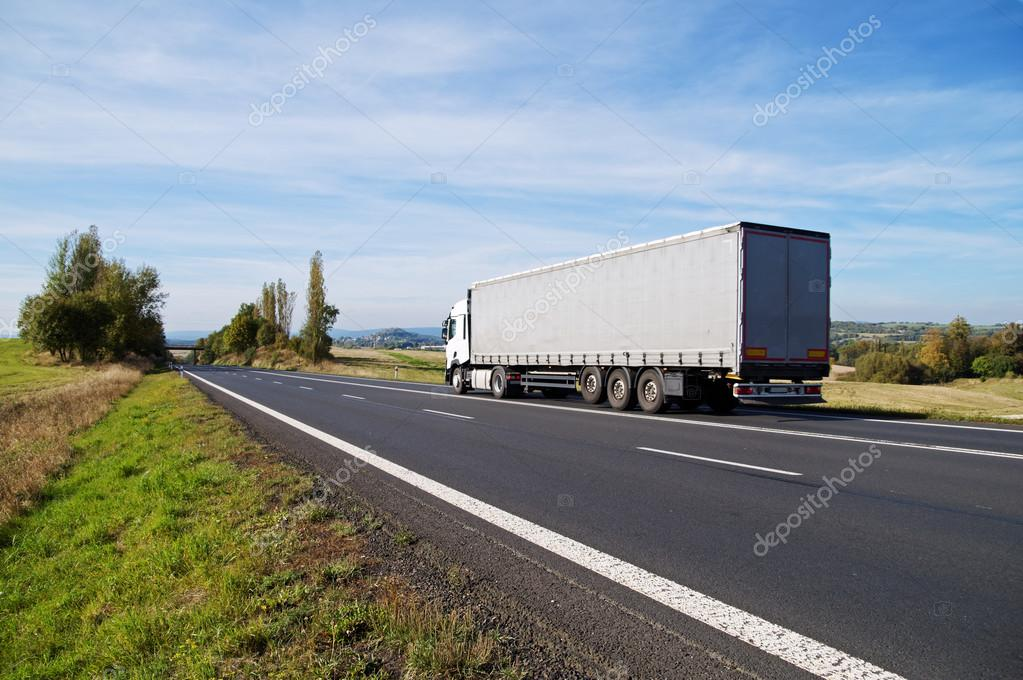 White truck travels on the asphalt road in the countryside.