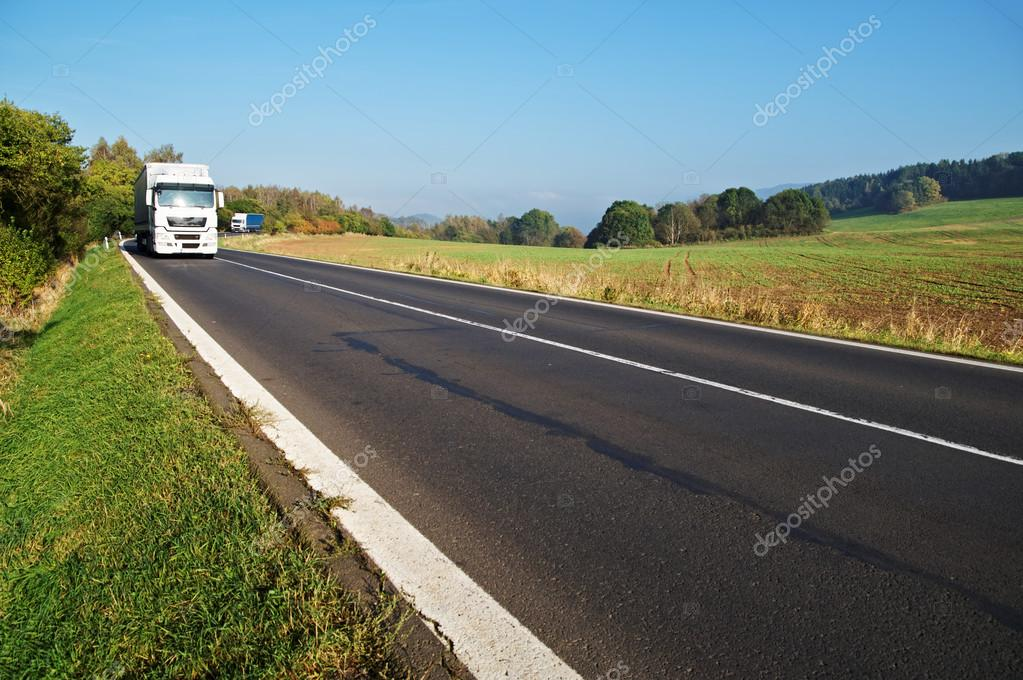 Asphalt road in a rural landscape, two truck
