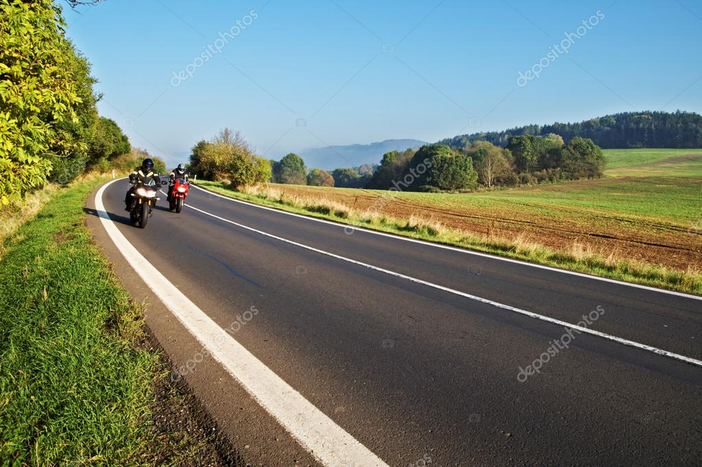 Country landscape with an asphalt road. Two motorcycles on the road.