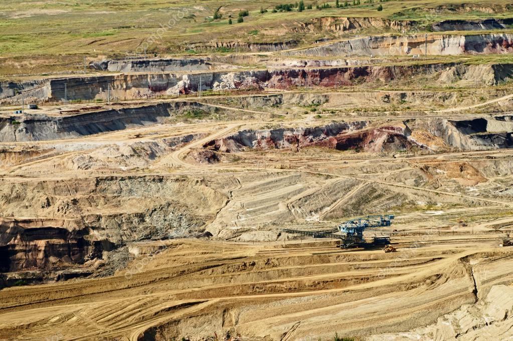 Bunk wall surface mine with exposed colored minerals and brown coal, the pit mining equipment